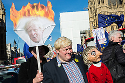 London, UK. 14th February, 2019. Boris Johnson lookalike Drew Galdron, also known as Faux BoJo, holds a Theresa May puppet as he joins anti-Brexit activists protesting outside the Houses of Parliament in Westminster.