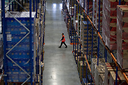 © Licensed to London News Pictures. 25/06/2013. London, UK. A Sainsbury's employee walks through the supermarket chain's newest state of the art logistics centre in Charlton, London, today (25/06/2013). Officially opened today, the logistics centre is currently responsible for supplying around 90 supermarkets in the South East and has so far created 60 jobs on site, with another 1000 to follow in the next three years. Photo credit: Matt Cetti-Roberts/LNP