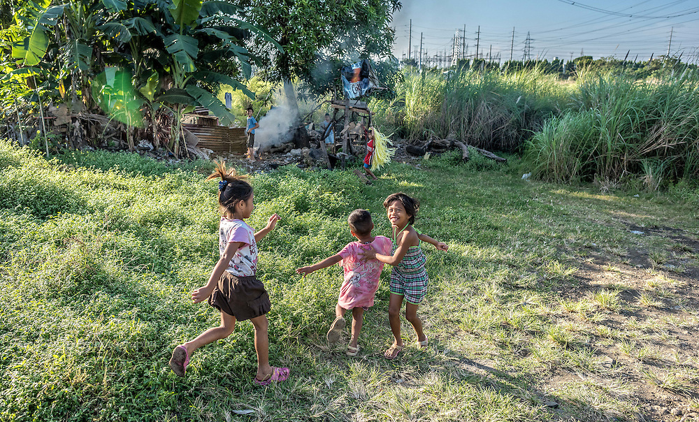 Life along the tracks by the gypsies and displaced people of Binan City. Playing between active railroad tracks and electricity generating power lines.