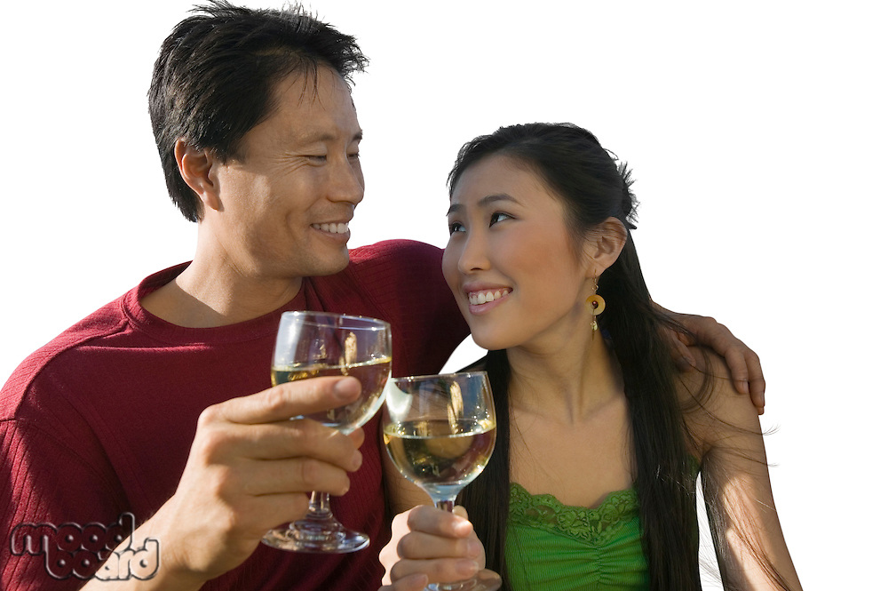 Happy mid-adult couple clinking their wineglasses against white background