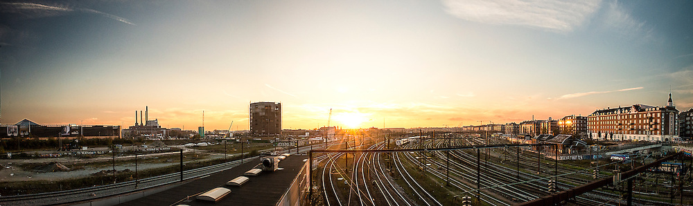 The sunsets over the train tracks at Dybbølbro in Copenhagen. To the left, the shopping centre Fisketorvet and Dong Energy's Power Plant can be seen.