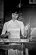 Young Vietnamese woman wearing an Ao Dai plays a dan bau (đàn bầu), a traditional string instrument, Khanh Hoa province, Vietnam, Southeast Asia