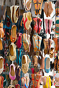 Decorative Moroccan slippers on sale inside the shopping souks of Asilah Medina, Northern Morocco, 2015-08-10.<br /><br />Asilah is a sleepy fishing town in the North of Morocco, just one hour south of Tangier. While not completely off Morocco's well-beaten path, it's often missed by travellers bound inland for Fez or Chefchaouen, yet has a uniquely alluring charm. With an immaculately restored medina that's re-painted vivid shades of blue & white each summer, Asilah has the feel of being Morocco's own Santorini - a great spot to see the more chilled out, seaside town life in Morocco.  <br /><br />Asilah is synonymous with art and the peaceful seaside town is home to over 50 resident artists. It is packed full of art galleries, studios and exhibition spaces with artists from around the country selling their work. Each summer, the town invites artists from across the globe to visit and take part in an annual arts festival. The festival begins in July and commences by the artists and locals re-painting the medina. They purposefully leave large spaces of the medina walls white-washed blank, ready for artists to create and design new murals and street art during the festival. Artwork can be found everywhere, including sketches and engravings etched onto doorways and walls by children. Large sections are even allocated for children to paint their own ideas and fun workshops are held encouraging children to work together and help paint new murals onto the walls. This is actually how Asilah began its synonymous relationship with art. In 1978 seven Moroccan artists were invited to the town to hold art classes for children, inviting them to draw on the walls of the medina. The festival goes on for a number of weeks showcasing a range of artistic disciplines, from music and poetry to performance and painting, and everything inbetween. Its mark is left on the town for the remainder of the year, as the murals and artwork are left spread throughout the medina, hiding down differ