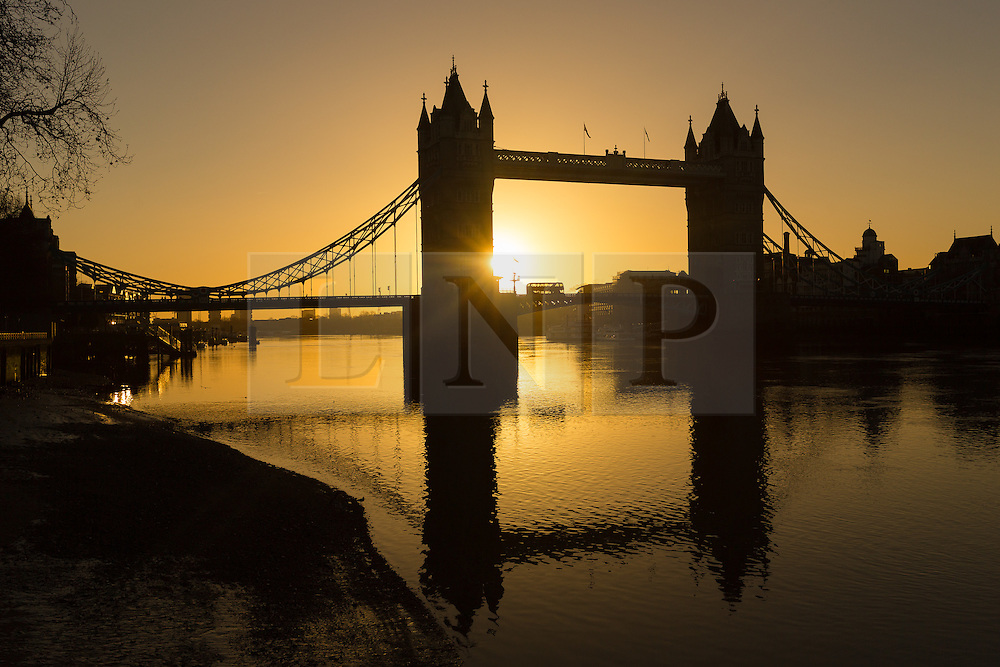 © Licensed to London News Pictures. 02/01/2017. LONDON, UK.  A bus passes during a golden sunrise behind Tower Bridge on the River Thames in London this morning during cold and clear weather following heavy rain yesterday.  Photo credit: Vickie Flores/LNP