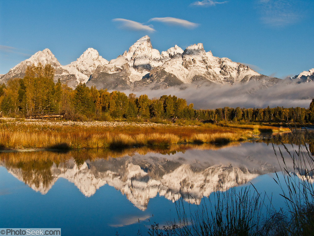 "Lenticular clouds (lens or wave clouds) cap the peaks of Grand Teton (13,766 feet or 4198.6 meters) and Teewinot. The Teton Range reflects in the Snake River at Schwabacher Landing in Grand Teton National Park, Wyoming, USA. Grand Teton National Park contains the major peaks of the 40-mile (64 km) Teton Range and part of the valley known as Jackson Hole, Wyoming. The Teton Range began their tectonic uplift 9 million years ago (during the Miocene Epoch), making them the youngest range in the Rocky Mountains. A parkway connects from Grand Teton National Park 10 miles north to Yellowstone National Park. Published in the book ""Mountain"" by Sandy Hill, 2011, Rizzoli International Publications Inc (p. 103), a benefit for the American Alpine Club Library."