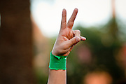 21 JUNE 2009 -- TEMPE, AZ: A man holds up his hand in the peace sign during a demonstration for Iranian democracy on the Arizona State University campus Sunday. About 300 people gathered on the Arizona State University campus in Tempe, AZ, Sunday night for a silent vigil to honor the people killed by Iranian security forces during prodemocracy election protests over the weekend.  PHOTO BY JACK KURTZ