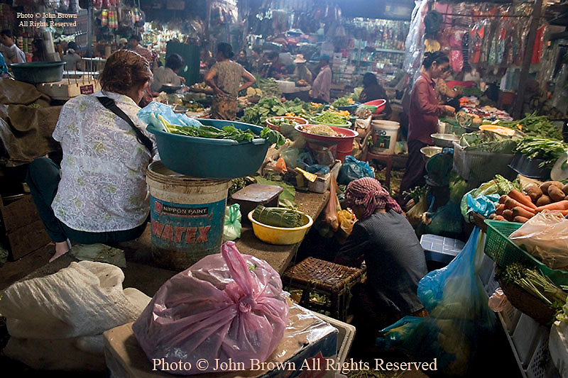 A woman vegetable vendor is preparing for food shoppers inside the Russian Market in Phnom Penh, Cambodia.
