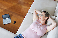 Woman lying down on couch laptop in background view from above.