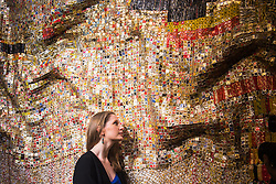Bonhams, Mayfair, London. A woman admires the detail of Peju's Robe, estimated at £450,000 - 550,000, by Ghanaian sculptor El Anatsui is made from thousands of pressed bottle tops to be auctioned at Bonhams post-war and Contemporary art sale. ///FOR LICENCING CONTACT: paul@pauldaveycreative.co.uk TEL:+44 (0) 7966 016 296 or +44 (0) 20 8969 6875. ©2015 Paul R Davey. All rights reserved.
