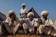 Rajusthani pastoralists at the Pushkar camel and livestock fair which takes place in the Hindu month of Kartik (October / November) ten days after Diwali (Festival of Lights). The pastoralists generally wear a white cotton dhoti (Strip of fabric tied into pants) and white jackets and turbans. The traditional pipe is called a 'Chilum'.<br /> Pushkar has always been the the region's main market for herdsman and farmers buying and selling camels, horses, indigenous breeds of cattle and even elephants. Over the years this annual trading event has increased in volume to become one of the largest in Asia. Temporary tents and campsites suddenly appear to accomodate the thousands of pilgrims, villagers and tourists. Entertainers and contests abound and a festive funfair atmosphere prevails over Pushkar during the Mela's 2 week duration. Thousands of men come first with their camels, horses and cattle and camp on the dunes to transact business. 3 days before the full moon the women arrive beautifully attired. The town of Pushkar is one of the holiest centers of Hinduism and houses one of the few Brahma Temples in India. It is one of the 5 essential pilgrimage centers which a Hindu must visit in his lifetime along with Badrinath, Puri, Rameshwaram and Dwarka. The 12 day fair culminates in a religious Hindu pilgrimage and reaches a crescendo on the night of the full moon (Purnima) when pilgrims take a dip in the holy lake.  <br /> Pushkar, Rajasthan. INDIA
