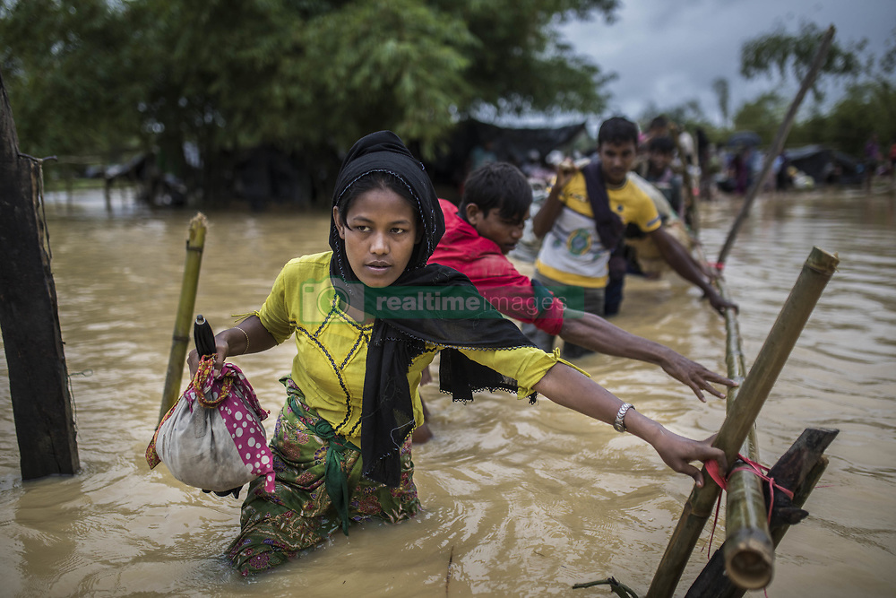 September 19, 2017 - Cox's Bazar, Chittagong, Bangladesh - Crossing a makeshift bridge over a swollen river, some of the Rohingya refugees have to leave their camps at Cox's Bazar due to rain and flooding. Many of the Rohingya fleeing the violence in Myanmar had travelled by boat to find refuge in neighboring Bangladesh. According to United Nations more than 400 thousand Rohingya refugees have fled Myanmar from violence over the last few weeks, most trying to cross the border and reach Bangladesh. (Credit Image: © Can Erok/Depo Photos/zReportage.com via ZUMA Wire)