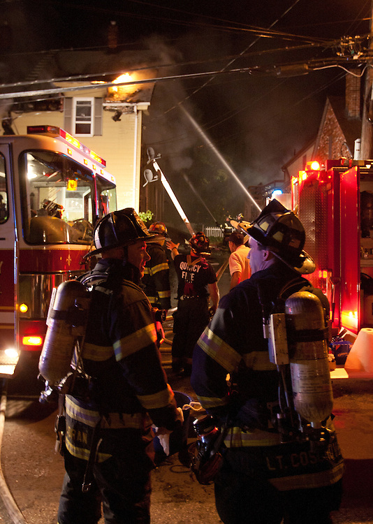 Quincy, MA 10/09/2011.Quincy Fire Department firefighters at the scene of a 2 alarm house fire at 44 Penn St. on Sunday night..Alex Jones / www.alexjonesphoto.com