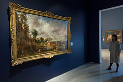 """© Licensed to London News Pictures. 11/01/2019. LONDON, UK. A staff member views """"The Opening of Waterloo Bridge ('Whitehall Stairs, June 18th, 1817')"""" by John Constable.  The painting is being shown with """"Helvoetsluys"""", 1832, by J.M.W. Turner (R) at The Royal Academy of Arts in Piccadilly for the first time since the artists clashed at the Summer Exhibition in 1832.  Turner allegedly added a small dab of red paint to his canvas, which he then converted into an image of a buoy floating in the sea. when he saw his painting next to Constable's.  The two works form """"He has been here and fired a gun"""": Turner, Constable and the Royal Academy, on display from 12 January to 31 March 2019.  Photo credit: Stephen Chung/LNP"""