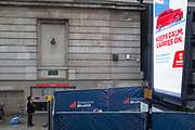 A bystander views a digital advertising billboard at London Bridge in Southwark, on 29th August 2018, in London, England.