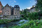 The Water of Leith river flows through Dean Village, the site of old watermills in a deep gorge, in Edinburgh, the capital city of Scotland, in Lothian on the Firth of Forth, Scotland, United Kingdom, Europe.