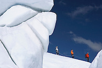 Mountain climbers hiking past ice formation