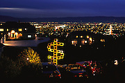 Silicon Valley, California. A sculpture made from recycled computers photographed on Observatory Drive, off Mt. Hamilton Road, overlooking the Silicon Valley and downtown San Jose. The houses in the photos are owned by people in high tech business: a high speed networking company that competes with Cisco, an Apple vice-president, and a software company executive. Neighbors volunteered their cars for the photo: Mercedes, Lexus, Corvette, and a second-car Volvo. After the shoot, the wife of the Apple executive asked that we store the sculpture in the two-story atrium of her house where it resided surrounded by a spiral staircase until donated to a museum. (1999).