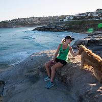 A woman pets a dog on the cliffs near the Gaerloch Reserve by Tamarama Beach along the Bondi to Bronte Coastal walk in Sydney, Australia.