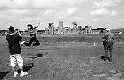 A tourist leaps in front of Stonehenge whilst having her photo taken.