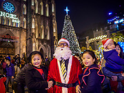 23 DECEMBER 2017 - HANOI, VIETNAM: A Vietnamese man dressed as Santa Claus poses for pictures with Vietnamese families in front of St. Joseph's Cathedral in Hanoi. The commercial and gift giving aspect of Christmas is widely celebrated in Vietnam and Vietnam's 5+ million Catholics celebrate the religious aspects of Christmas.     PHOTO BY JACK KURTZ