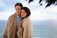 Couple covered by blanket standing by sea portrait