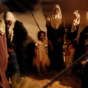 Interior of a Bedouin tent. The Bedouin women usually wear brightly coloured long dresses but when they go outside they dress in an 'abaya' o Mandraga (a long black coat sometimes covered with shiny embroidery) and they will always cover their head and hair when they leave their house with a 'tarha',a black shaw.   The younger generations cover their face simply with their 'tarha' (shawl). Both clothing and tattoos determine their status and marital status.