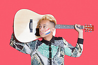 Teenage boy carrying guitar with Dutch flag on his face over pink background