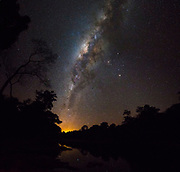 The Milky Way seen from Brazilian rainforest along the shore of Rio Cristalino, southern Amazon. Mosaic of 2 images. The orange glow is the lights from the city of Alta Floresta. Mars and Saturn together with the orange star Antares form the triangle just to the right (west) of the galactic centre.