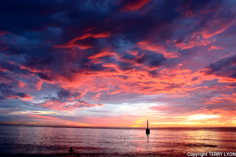 A brilliant red sky sunset with one swimmer looking toward the Cottesloe pylon.