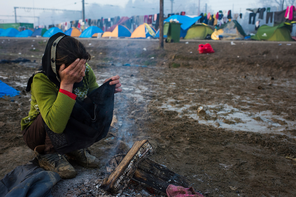 A Yazidi woman tries to dry her child's clothes on a fire at a dawn in a refugee camp on the Macedonian (FYROM) border on March 11, 2016 in Idomeni, Greece.