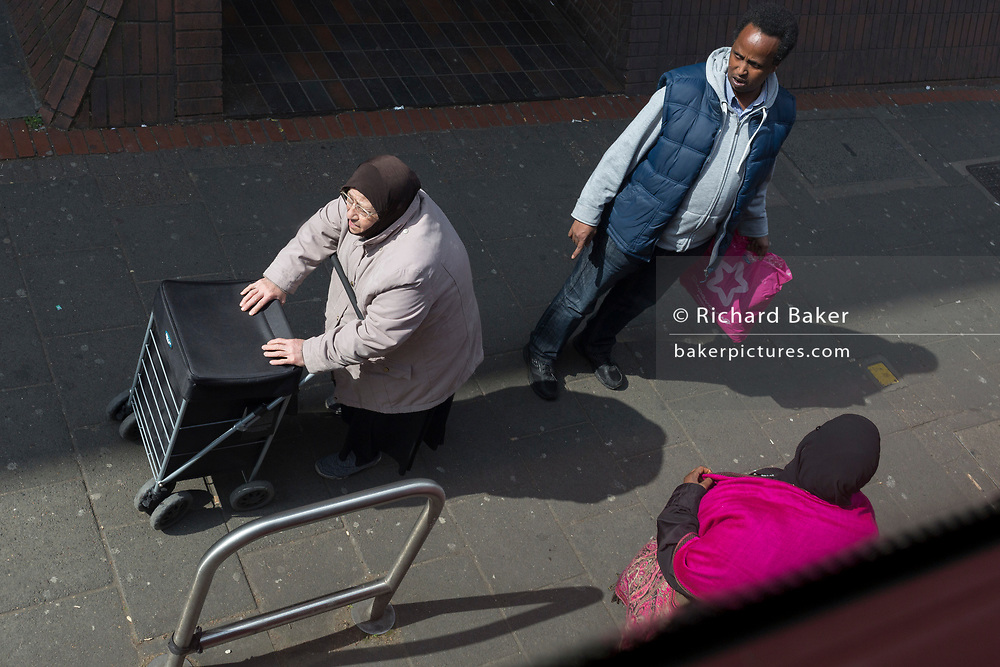 An elderly lady and passers-by on the Walworth Road in Southwark, on 28th March 2019, in London, England