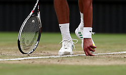 Novak Djokovic picks at the grass near the baseline of centre court during his match against Adrian Mannarino on day eight of the Wimbledon Championships at The All England Lawn Tennis and Croquet Club, Wimbledon.