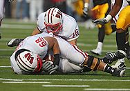 October 23 2010: Wisconsin Badgers offensive linesman Gabe Carimi (68) and Wisconsin Badgers quarterback Scott Tolzien (16) fall on a loose ball during the first half of the NCAA football game between the Wisconsin Badgers and the Iowa Hawkeyes at Kinnick Stadium in Iowa City, Iowa on Saturday October 23, 2010. Wisconsin defeated Iowa 31-30.