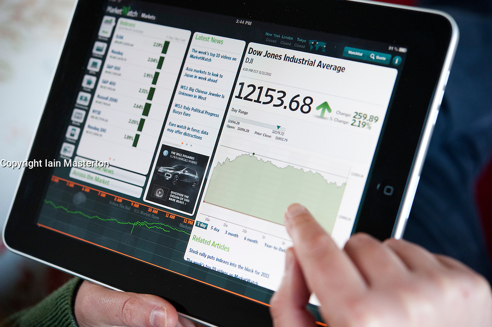 Woman using iPad tablet computer  to check stock market prices of Dow Jones Industrial Average index