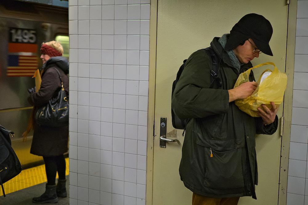 Man eating on subway platform, Times Square, New York, NY, US