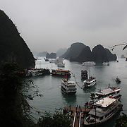 An elevated view of tourist junks visiting Surprise Cave, Ha Long Bay, Vietnam. The bay consists of a dense cluster of 1,969 limestone monolithic islands. Ha Long Bay, is a UNESCO World Heritage Site, and a popular tourist destination. Ha Long, Bay, Vietnam. 11th March 2012. Photo Tim Clayton