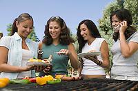 Four women around outdoor grill.