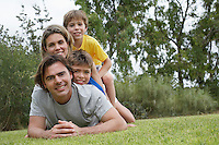 Portrait of couple with two sons (6-11) lying on top of each other on lawn