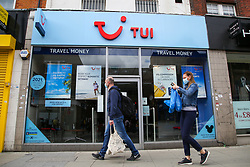 © Licensed to London News Pictures. 13/05/2020. London, UK. Members of the public wearing face coverings walk past a Tui branch in north London. Tui Group is to cut 8,000 jobs worldwide after losing £747m in 2020 due to COVID-19. Photo credit: Dinendra Haria/LNP