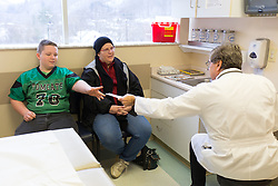 1/27/15 10:21:24 AM -- Louisa, KY, U.S.A  -- Nate Castle, 12, left, is given a prescription by Dr. Mazen Jaafar, right, for a cough on Tuesday,  at his office in Prestonsburg on Tuesday.<br /> <br /> Cheryl is a recent recipient of the high-tech device, can now do many tasks she was unable to do when her epileptic seizures became more severe and more frequent. Now she's getting back to a normal life.<br /> <br />  --    Photo by Jonathan Palmer, Freelance