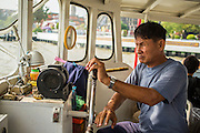 21 NOVEMBER 2012 - BANGKOK, THAILAND: A ferry captain steers his boat across the Chao Phraya River. A network of ferries connect the Thonburi section of Bangkok to Bangkok proper, crossing the Chao Phraya River. The fare is 3 Thai Baht, about $ 0.15 (US). The boats are the fastest way to get from north to south in Bangkok. Thousands of people commute to work daily on the Chao Phraya Express Boats and fast boats that ply Khlong Saen Saeb. Boats are used to haul commodities through the city to deep water ports for export.    PHOTO BY JACK KURTZ
