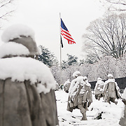 The Korean War Veterans Memorial on the National Mall on a winter morning after heavy snow. The Korean War Veterans Memorial, unveiled in 1992, sits on the northwestern end of the National Mall, not far from the Lincoln Memorial. It consists of several elements designed by different people and groups. It has a triangular footprint with the main elements being ?The Column? consisting of 19 stainless steel solders, each over 7 feet tall, and a reflective granite wall etched with the faces of thousands of Americans who lost their lives in the war. At one end of the triangle, behind the soldiers, is a grove of trees. At the other is a large American flag and a small Pool of Remembrance. Among the designers were Frank Gaylord (the soldiers) and Louis Nelson (the reflecting granite wall).
