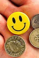 Smiley faced yellow badge in palm of male hand with British coins. Signed model release.