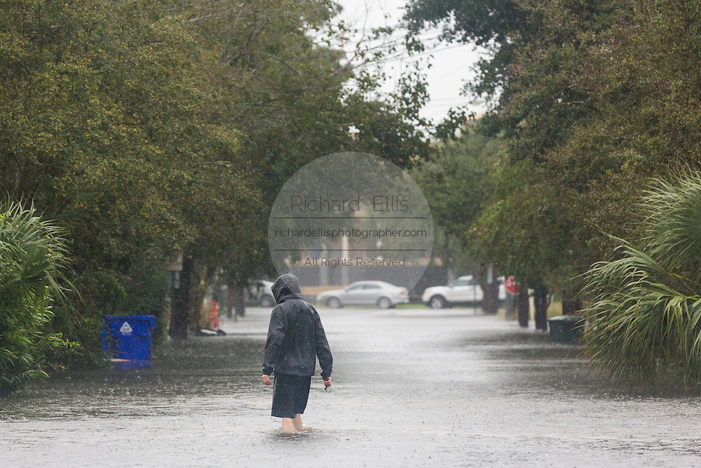 Residents walk across a flooded street in the historic district as Hurricane Joaquin brings heavy rain, flooding and strong winds as it passes offshore October 3, 2015 in Charleston, South Carolina.