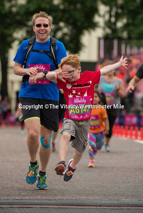 Runners from Family Race waves at the finishing line outside Buckingham Palace at The Vitality Westminster Mile, Sunday 28th May 2017.<br /> <br /> Photo: Thomas Lovelock for The Vitality Westminster Mile<br /> <br /> For further information: media@londonmarathonevents.co.uk