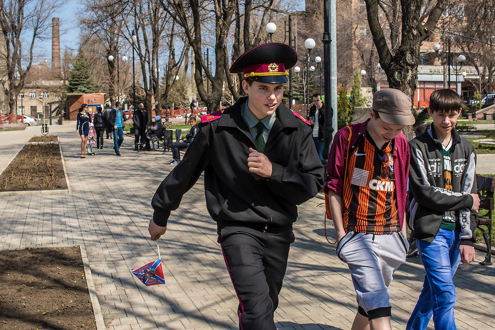 A boy that is part of a youth military regiment shows his friends his technique for marching while holding the flag of the self-declared independent republic of Novorossiya on Orthodox Easter, Sunday, April 12, 2015 in Donetsk, Ukraine.