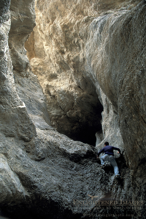 Hiker climbing up rock wall at Grotto Canyon, Death Valley National Park, California