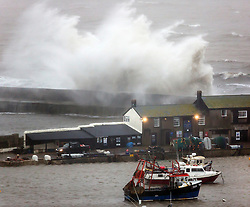 © Licensed to London News Pictures. 27/01/2016. Lyme Regis, UK. Large waves crash over the Cobb at Lyme Regis harbour in  Dorset, south west England at high tide. The tail end of storm Jonas continues to hit the UK, bringing torrential rain and gales. Photo credit: Peter Macdiarmid/LNP