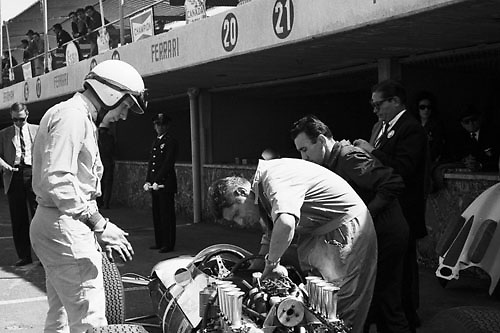 World Champion John Surtees watches Ferrari mechanic Giulio Borsari at work in pit lane, 1964 Gran Premio de Mexico; Photo by Pete Lyons 1964/ © 2014 Pete Lyons / petelyons.com