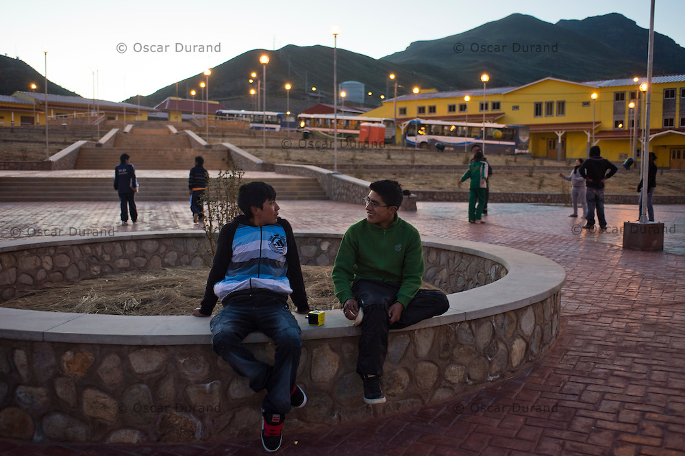Jose Luis De La Cruz,18, and Nando Ramos,17, left to right, chat in a plaza in the newly built town of Carhuacoto in the central Peruvian Andes. Chinese mining company Chinalco built this town to relocate the residents of Morococha, where they plan to mine for copper and other minerals. Chinalco built houses and also public buildings such as schools and churches.